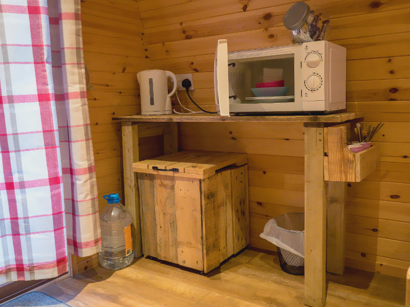 Glamping Pod kitchenette with bin, water carrier, kettle and microwave