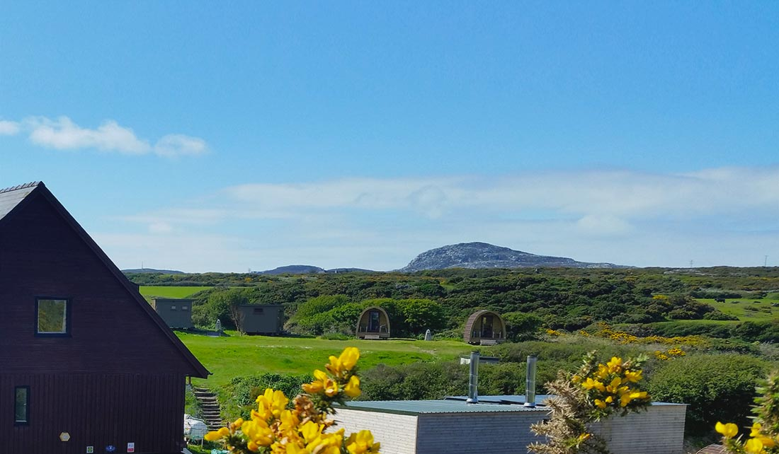 Panoramic view Glamping Pod site from a distance with Holyhead Mountain (Mynydd Tŵr) in the background
