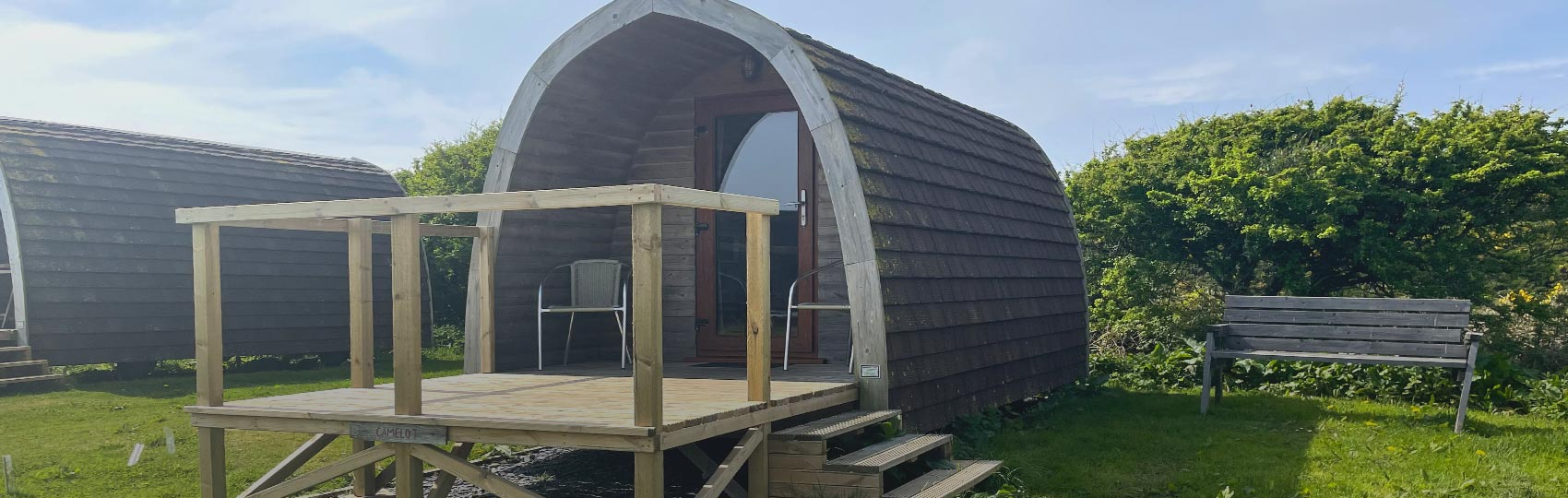 Lady relaxing in the porch of a glamping Pod on North Wales hill