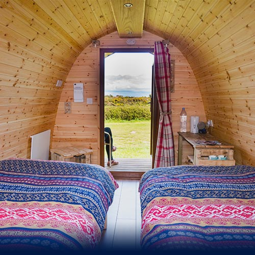 Two Scandinavian dressed beds in a Glamping Pod with a view of the hills through the open front door