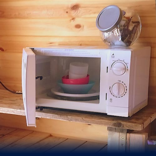 Microwave with kitchen crockery and utensils inside
